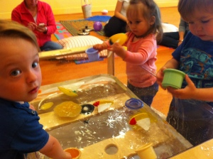 Tots at Genius: A Baby Academy in Seattle sharing a water play experience and toys.